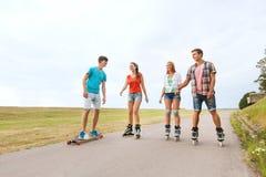 Les adolescents heureux avec fait du roller et des longboards Images stock