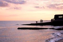 Les adolescents jouant au coucher du soleil sur les eaux affilent silhouetté par le soleil Image libre de droits