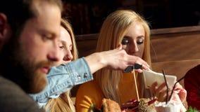 Les adolescents ont plaisir à manger des hamburgers dans le café Les amis se passent des serviettes banque de vidéos