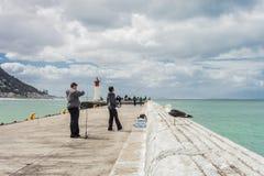 Les adolescents pêchant avec la tige et tournoient un mur de port photos stock