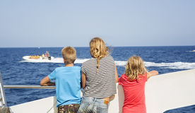Les adolescents regardent la mer de la plate-forme de bateau Image libre de droits