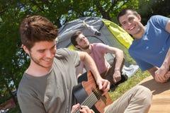 Les adolescents s'approchent de la tente jouant la guitare Photographie stock libre de droits