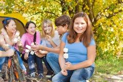 Les adolescents s'asseyent sur le terrain de camping avec des bâtons de guimauve Images stock