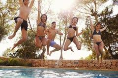 Les adolescents sautant dans une piscine extérieure regardent à l'appareil-photo, Ibiza Image libre de droits