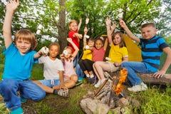 Les ados avec des bras vers le haut de feu proche tiennent la guimauve Photos libres de droits