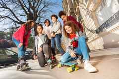 Les ados avec la planche à roulettes ou fait du roller dans le paysage urbain Image stock