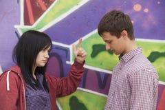 Les ados de conflit s'approchent du mur de graffiti. Photographie stock libre de droits