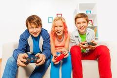 Les ados heureux tiennent des manettes et jouent la console de jeu Photo libre de droits