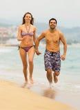 Les adultes courant dans les vêtements de bain sur la mer ondule Photos libres de droits