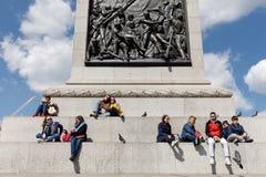 Les adultes et les enfants se reposent à la base de la colonne du Nelson Image libre de droits