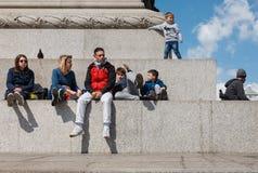 Les adultes et les enfants se reposent à la base de la colonne du Nelson Image stock