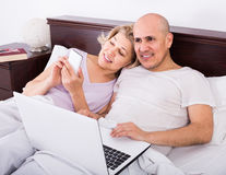 Les adultes lisant ensemble des actualités de carnet et de smartphone dans soient Photos libres de droits