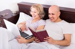 Les adultes lisant ensemble des actualités de carnet et de smartphone dans soient Photo stock