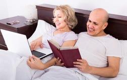 Les adultes lisant ensemble des actualités de carnet et de smartphone dans soient Image libre de droits
