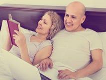 Les adultes lisant ensemble des actualités de carnet et de smartphone dans soient Photographie stock