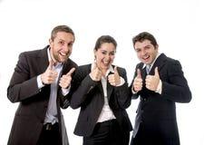 Les affaires heureuses fonctionnent le sourire avec leurs pouces  Photos stock