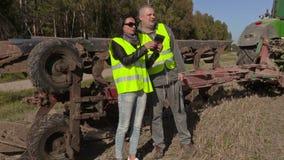 Les agriculteurs couplent parler près du tracteur sur le champ banque de vidéos