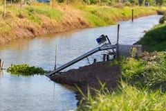 Les agriculteurs pompant l'eau au riz de jasmin met en place avec le moteur Image libre de droits