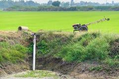 Les agriculteurs pompant l'eau au riz de jasmin met en place avec le vieux tracteur Photographie stock libre de droits