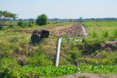 Les agriculteurs pompant l'eau au riz de jasmin met en place avec le vieux tracteur Photos stock