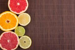 Les agrumes ont coupé des oranges de fond, citrons, les chaux, pamplemousse sur un fond en bois Photos libres de droits