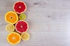 Les agrumes ont coupé des oranges de fond, citrons, les chaux, pamplemousse sur un fond en bois lumineux Photo libre de droits