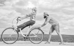 Les aides d'homme gardent l'équilibre et montent le vélo Comment apprendre à monter le vélo comme adulte Fille faisant un cycle t photographie stock libre de droits