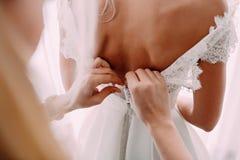 Les aides de demoiselle d'honneur attachent une robe de mariage la jeune mariée avant la cérémonie Préparation de matin avant le  photographie stock libre de droits