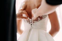 Les aides de demoiselle d'honneur attachent une robe de mariage la jeune mariée avant la cérémonie Proue d'étoile bleue avec la b image stock