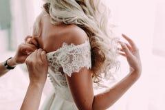 Les aides de demoiselle d'honneur attachent une robe de mariage la jeune mariée avant la cérémonie Proue d'étoile bleue avec la b photo libre de droits
