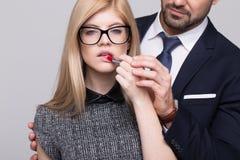 Les aides de main d'homme appliquent le rouge à lèvres rouge à la femme blonde Photographie stock libre de droits