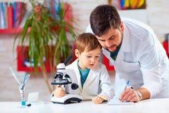 Les aides de professeur badinent pour entreprendre l'expérience avec le microscope photographie stock