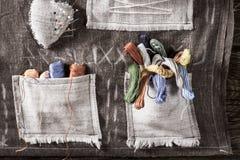 Les aiguilles et les fils colorés dans le tapis travaillent la poche Images stock