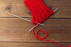 Les aiguilles et le fil de tricotage au coeur forment sur le bois Photo libre de droits