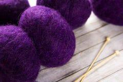 Les aiguilles pourpres de fil et de tricotage sur la table Photos stock