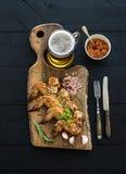 Les ailes de poulet frit sur la portion rustique embarquent, épicé Photo stock