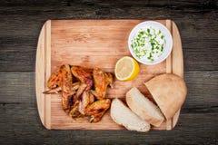 Les ailes de poulet grillées délicieuses avec de la sauce, le citron et le pain à ail sur une planche à découper sur le fond rust Images stock
