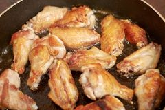 Les ailes de poulet ont fait frire dans la casserole avec de l'huile chaude, nourriture faite maison photo libre de droits