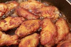 Les ailes de poulet ont fait frire dans la casserole avec de l'huile chaude, nourriture faite maison images stock