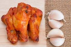Les ailes de poulet sur les planches à découper en bois avec l'ail sur le front renvoient Photographie stock libre de droits