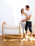 Les ajouter à la femme enceinte étreignent avec le berceau de chéri Images libres de droits