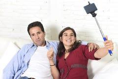 Les ajouter à la femme prenant la photo de selfie avec l'homme de téléphone portable et de bâton ont fatigué et malade des photos Photographie stock