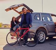 Les ajouter à la vitesse simple vont à vélo près de la voiture avec le tronc ouvert Photographie stock libre de droits