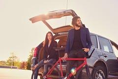 Les ajouter à la vitesse simple vont à vélo près de la voiture avec le tronc ouvert Photos stock