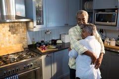 Les ajouter affectueux aux yeux ont fermé l'embrassement tout en se tenant dans la cuisine Photo libre de droits