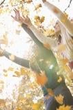 Les ajouter aux bras ont soulevé apprécier les feuilles d'automne en baisse en parc Photographie stock libre de droits