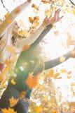 Les ajouter aux bras ont soulevé apprécier les feuilles d'automne en baisse en parc Image stock