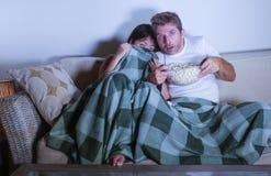 Les ajouter de métis à la femme coréenne asiatique et à l'homme blanc observant ensemble le film d'horreur de télévision ont effr Photographie stock