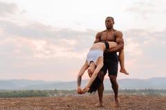Les ajouter gymnastiques de métis aux corps musculaires parfaits dans la danse de vêtements de sport sur des montagnes aménagent  Photo libre de droits