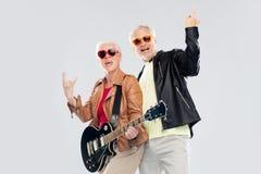 Les ajouter supérieurs à la guitare montrant la main de roche signent Images stock